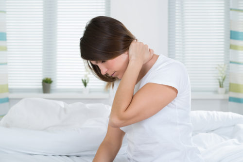Young Woman Suffering From Neck Pain Sitting On Bed